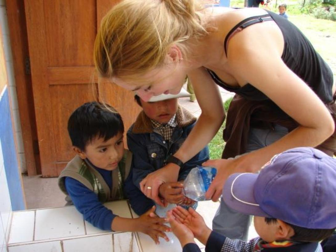 Projects Abroad volunteer shows a young boy how to clean his hands as part of hygiene care in Peru.